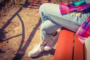 39811132cc57e1a3533a13c1da8d0bf7_s スニーカーを履いて足を組んで座る女性 ジーンズ ベンチ
